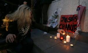 A woman pays tribute during a gathering at the Place de la Republique in Paris.