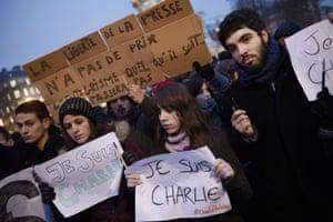 People hold Je Suis Charlie placards at the Place de la Republique