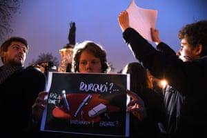 """A man holds a placard reading """"Why"""" at the Place de la Republique in Paris"""