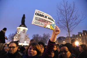 A woman holds up the Charlie Hebdo newspaper at the Place de la République in Paris