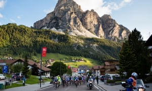 A group of cyclists ride by a mountain during the Maratona dles Dolomites race, Italy