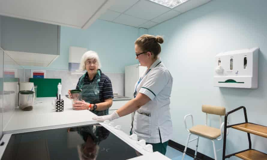 Occupational therapist Amy Hemus helps Angela Rankin, 68, who suffered a stroke a week ago, in a purpose-built kitchen within Addenbrooke's hospital.