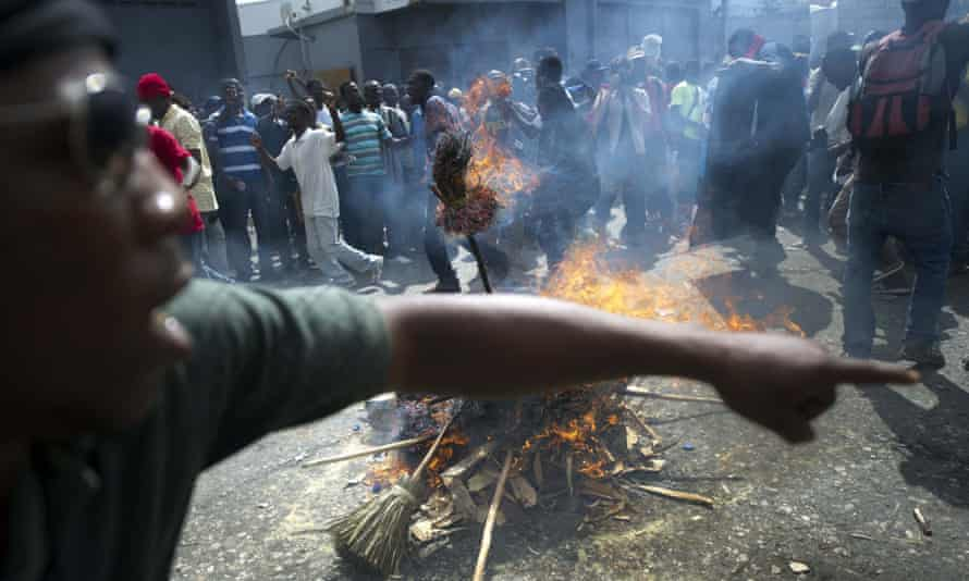 Demonstrators perform a voodoo ceremony prior to a protest against the government of President Michel Martelly, in Port au Prince, on November 25, 2014. Protesters marched through the streets calling for the resignation of the Haitian leader.