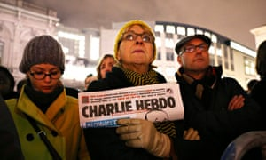 A woman holds a copy of Charlie Hebdo
