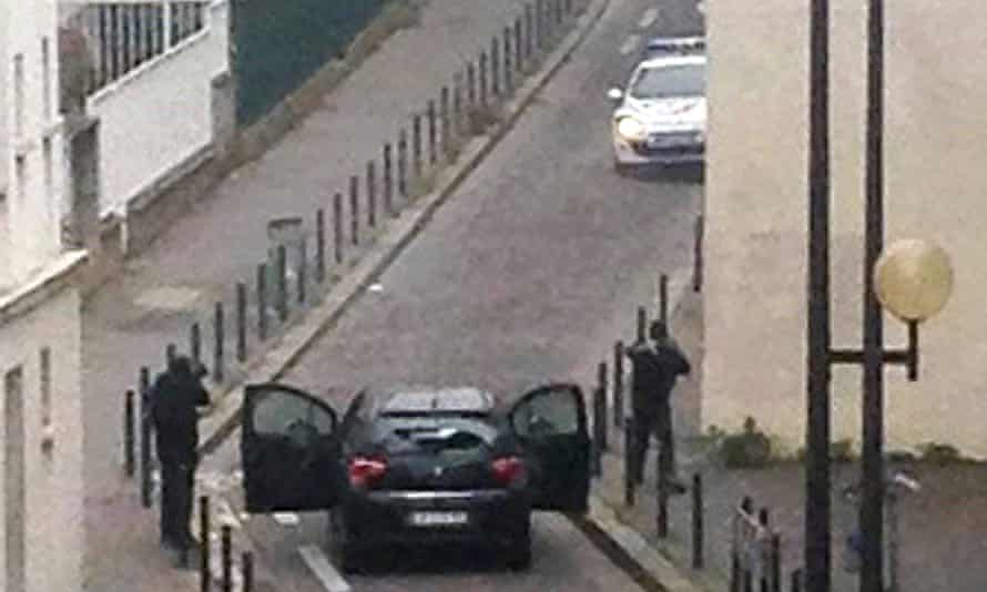 Armed gunmen face police officers near the offices of the French satirical newspaper Charlie Hebdo, in Paris.