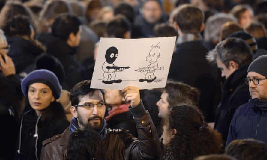 A man holds a drawing during a vigil for victims of the shootings, at Place de la Republique in Paris.