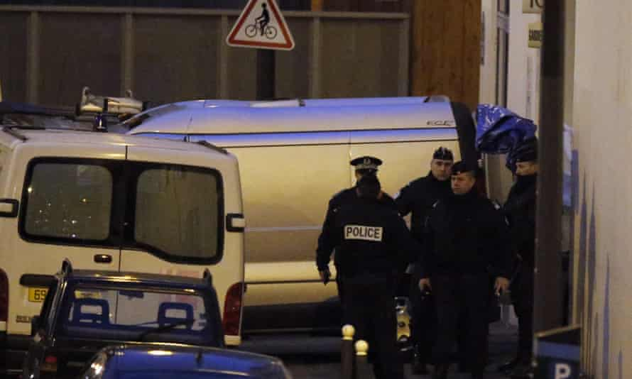 French police  stand next to funeral hearse in front of the entrance of the Paris offices of Charlie Hebdo.