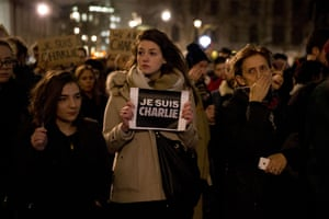 People hold up pens and posters reading Je Suis Charlie In Trafalgar Square, London to show solidarity with those killed in the attack the french newspaper Charlie Hebdo