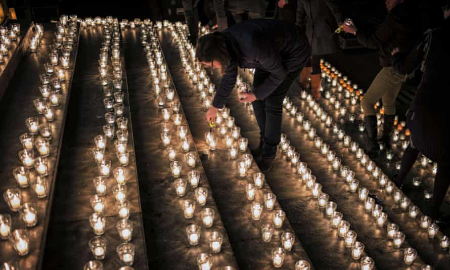 A woman lights a candle during a vigil in Lyon following an attack on Charlie Hebdo.