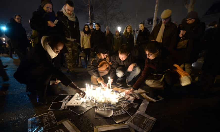 People light candles during a gathering to show solidarity for the victims of the attack on the offices of the satirical weekly, Charlie Hebdo.