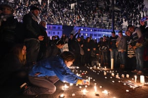 People gather to light candles under large mirror panels at the Old Port of Marseille