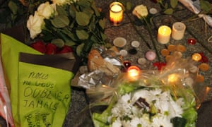 Flowers and candles on the pavement near the offices of Charlie Hebdo in Paris.