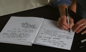 People sign a book of condolence in Melbourne where about 1000 people gathered at a vigil for the victims of the Charlie Hebdo attack.