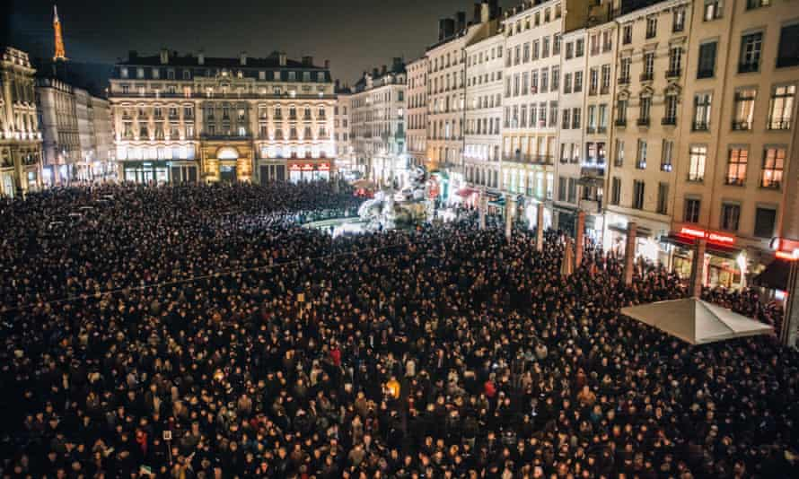 About 15,000 people take part in a vigil in Lyon, France to mourn the 12 people killed.