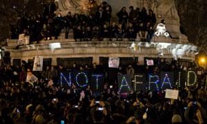 A sign reads 'not afraid' as thousands gather for a vigil on Place de la Republique in Paris on Wedn