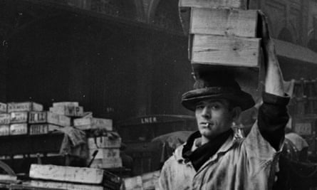 A porter at Billingsgate fish market in London, carries a load from the street into the market, April 1939.