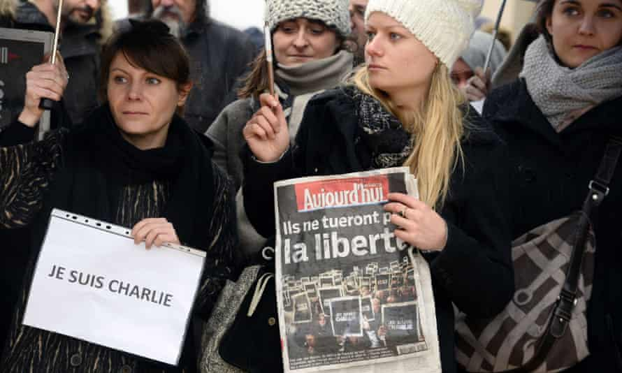 A woman, left, holds a sign reading 'Je suis Charlie'