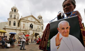 A Filipino vendor sells Pope Francis souvenirs in front of a church in Manila, Philippines