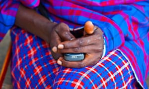 Maasai tribesman using a mobile phone in the Masai Mara, Kenya