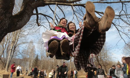 Belarusian women play on a swing at a Slavic