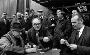This photograph shows poker playing during a sit-in at Bredbury Steel works, Manchester, April 1972. 12,000 strikers were involved in sit-ins in dozens of factories across the city. The men at Bredbury Steel, photographed here by Don McPhee, organised themselves in nine shifts of 60 men, each on duty for eight hours.