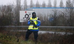 A police officer stands along a road  holding a gun