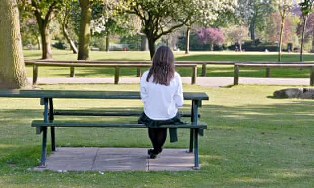 Girl sitting alone on park bench