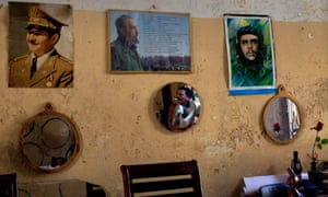A Havana man is reflected in a mirror hanging on his wall covered with photographs of (L to R) Raul Castro, Fidel Castro, and fellow revolutionary Ernesto Che Guevara.