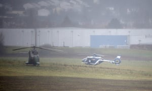 A police helicopter and the French Special Police Forces wait in fields
