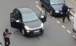 Gunmen flee the offices of Charlie Hebdo magazine in Paris.