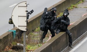 Members of the French police special force advance with their equipment on the Paris ring road near the scene