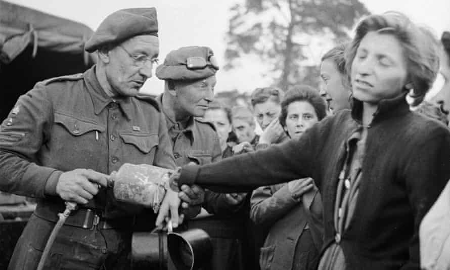 A British soldiers sprays DDT on a woman liberated from Bergen-Belsen