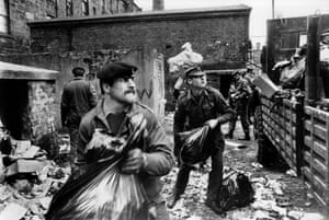 This photograph shows troops from the Royal Scots Regiment clearing rubbish in Glasgow, April 1975. 2,500 troops were involved in removing rubbish over a three week period following a strike by dustcart drivers. The soldiers each received a mug and a miniature bottle of whisky in return for their help in cleaning up the city.