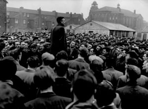 Strike meeting, Manchester Docks, March 1955. This photograph depicts John McShane, temporary Blue Union (National amalgamated Stevedores and Dockers Union) organiser for the Port of Manchester addressing strikers on waste ground near the Manchester docks. Work had recently stopped on 88 ships in Merseyside and Manchester with strikes breaking out over the employment of dockers who had left the TGWU to join the rival Blue Union.