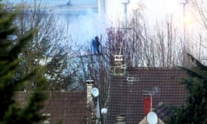 Smoke rises as special forces enter the building where the suspects were holding a hostage