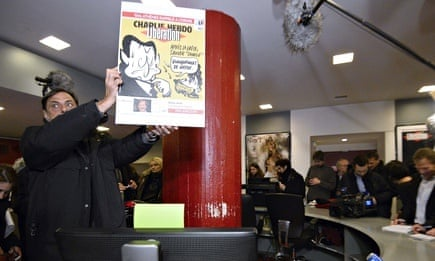 A man holds the cover of an issue of Libération bearing the name of Charlie Hebdo, as the magazine's staff gathered for the first time following Wednesday's massacre