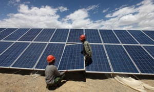 Workers install a solar panel at a photovoltaic power station in Aleteng village, northwest China. Job creation is an example of an economic co-benefit of tackling climate change.