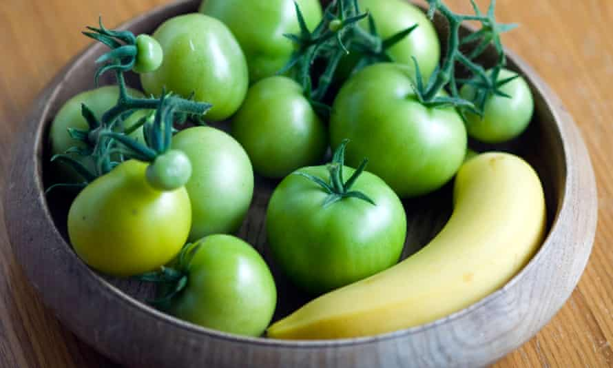 Placing tomatoes next to a banana will help them ripen, but speed things up by placing them in a bag or cardboard box.