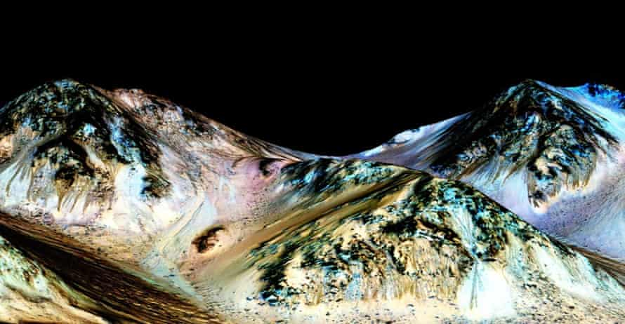 A handout image made available by NASA on September 27, 2015, shows dark, narrow, 100 meter-long streaks called recurring slope lineae flowing downhill on Mars, inferred to have been formed by contemporary flowing water.