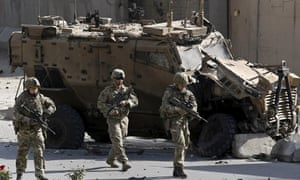 Nato soldiers in front of a damaged military vehicle after a suicide car bomb explosion in Kabul.