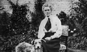Black and white photo; Cavell is sat on a dining chair outside, a garden wall behind her. Her hair is tied back, slightly bouffant, and she is wearing a striped pale blouse, long dark skirt, and wide dark tie or cravat. She is petting a large dog.