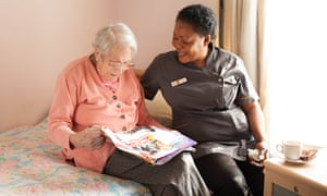 A care-support worker helps an old lady read a magazine on a bed