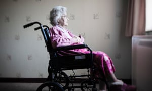 An elderly lady sits in a wheelchair looking out of the window