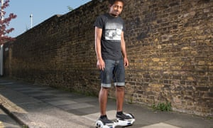 Jay standing on a Swegway wheeling device next to a brick wall