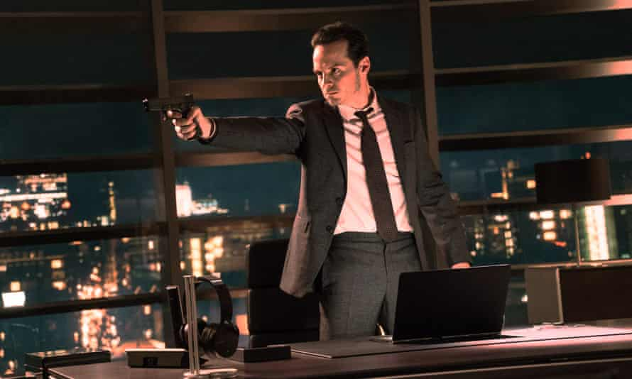Andrew Scott as Max Denbigh in Spectre points a gun in a high rise office, windows behind him, a hard expression on his face.