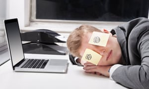 Young person asleep at desk with post-it notes with drawings of eyes over his eyes