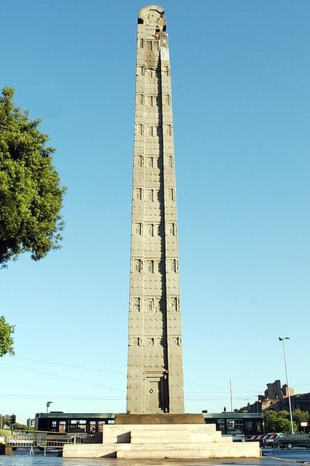 The 1,700-year-old Axum Obelisk, pictured against a clear, azure sky in a piazza in Rome, Italy