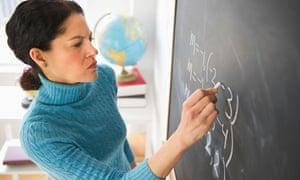 Mature woman writing on blackboard.
