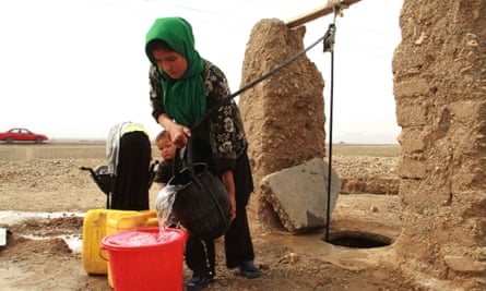 An Afghan girl gets drinking water from a community well, in Herat, Afghanistan.
