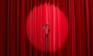 Microphone in spots light on empty stage with red curtain behind